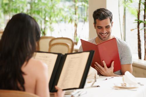 Bild: Mann und Frau mit Speisekarte am Tisch bei der Auswahl der Speisen